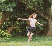 Young girl with arms open enjoying her freedom at the park so happy relax dance.  Royalty Free Stock Image