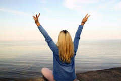Young girl with arms raised above the head on the shore Stock Image