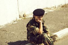 Young girl in army camouflage. Young girl child with pretty sad thoughtful face in army camouflage ammunition and black beret sitting on stone ground outdoor stock photo