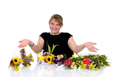 Young girl arranging flowers. On reflective surface, white background, studio shot Stock Images