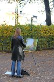 Girl artist painting an autumn landscape. Young girl artist painting an autumn landscape on canvas with the easel in a city Park stock photos