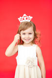 Young girl as little princess carnival costume. White skirt and crown. Vertical portrait isolated on red background stock photo