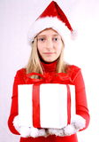 Young girl as Mrs. Santa gives a gift Stock Image