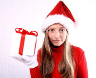 Young girl as Mrs. Santa holding a gift Royalty Free Stock Image