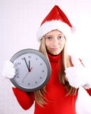 Young girl as Mrs. Santa in red with clock Stock Photo