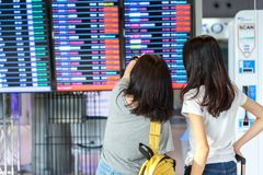 Young girl asian together traveler. Looking timetable with carrying, suitcase luggage and passenger for tour travel booking ticket flight in airport stock photography