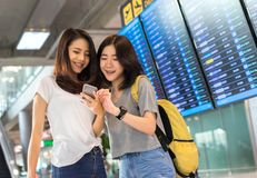 Young girl asian together using mobile smartphone. With carrying hold suitcase luggage and passenger for tour travel booking ticket flight in airport stock photo