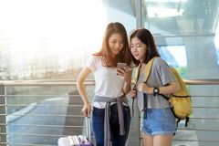 Young girl asian together using mobile smartphone. With carrying hold suitcase luggage and passenger for tour travel booking ticket flight in airport royalty free stock photo
