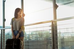 Young girl asian traveler backpack with carrying. Hold suitcase luggage and passenger for tour travel booking ticket flight in airport international vacation stock photography