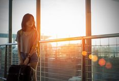 Young girl asian traveler backpack with carrying. Hold suitcase luggage and passenger for tour travel booking ticket flight in airport international vacation stock photo