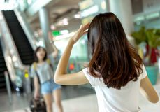 Young girl asian traveler finding friend. With carrying hold suitcase luggage and passenger for tour travel booking ticket flight in airport international stock photo