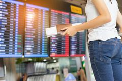 Young girl asian traveler holding passport. Looking flight board booking ticket with carrying hold suitcase luggage and passenger for tour travel in airport royalty free stock photos