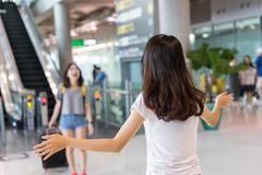 Young girl asian traveler hugging friend. With carrying hold suitcase luggage and passenger after tour travel booking ticket flight in airport international stock photography