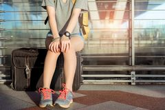 Young girl asian traveler sitting with carrying. Hold suitcase luggage and passenger for tour travel booking ticket flight in airport international vacation stock image