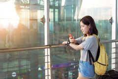 Young girl asian traveler using mobile smartphone. With carrying hold suitcase luggage and passenger for tour travel booking ticket flight in airport stock photography