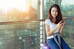 Young girl asian traveler using mobile smartphone. With carrying hold suitcase luggage and passenger for tour travel booking ticket flight in airport royalty free stock photography