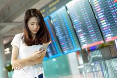Young girl asian traveler using mobile smartphone. With carrying hold suitcase luggage and passenger for tour travel booking ticket flight in airport stock photo