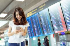 Young girl asian traveler using mobile smartphone. With carrying hold suitcase luggage and passenger for tour travel booking ticket flight in airport stock image