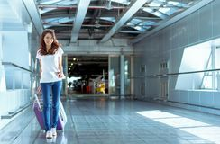Young girl asian traveler walking with carrying. Hold suitcase luggage and passenger for tour travel booking ticket flight in airport international vacation stock photos