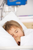 Young girl asleep in Accident and Emergency bed. Sucking her thumb Royalty Free Stock Photo