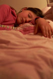 Young Girl Asleep In Bed At Night Stock Photo