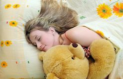 Young girl asleep in her bed with a teddy bear Stock Image