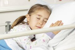 Young girl asleep in hospital bed stock photos