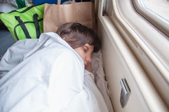 Young girl asleep in a second-class train carriage Stock Images