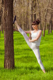 Young girl athlete doing stretching in a tree on the grass Stock Photos