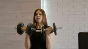 Young girl athlete performs exercises with dumbbells on a heavy workout in the fitness room. stock video footage
