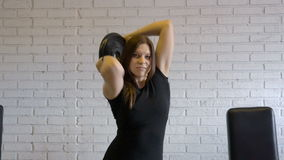 Young girl athlete performs exercises with dumbbells on a heavy workout in the fitness room. stock footage