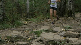Young girl athlete running in forest on rocks trail. Zlatoust, Russia - August 28, 2016: young girl athlete running in forest on rocks trail during Mountain stock video