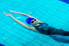 Young girl athlete swimming under water after start, sprint distance Royalty Free Stock Photography