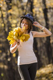 Young girl in autumn forest with a bouquet of  mapple leaves Stock Photo