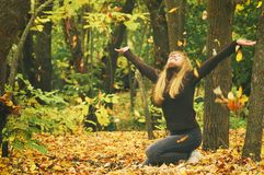 Young girl in autumn forest, throws yellow leaves, toned photo Royalty Free Stock Photo