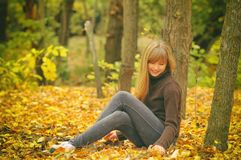 Young girl in autumn forest, throws yellow leaves, toned photo Stock Photo
