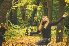 Young girl in autumn forest, throws yellow leaves, toned photo Royalty Free Stock Images
