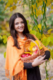 Young girl in autumn park with a basket of apples Stock Photography