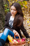 Young girl in autumn park with a basket of apples Stock Photos