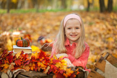 Young girl in autumn park with books, bouquet and little pumpkin Royalty Free Stock Photo