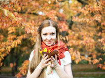 Young girl in autumn park with flowers Royalty Free Stock Image