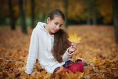 Young girl in autumn park playing with leaf Stock Photography