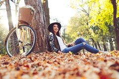 Young girl in autumn scenery. Beautiful woman outdoors in sunny day Royalty Free Stock Image