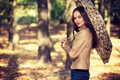 Young  girl in autumn scenery with umbrella. Stock Images