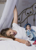 Young girl awakening and stretching on the bed after good night sleep Royalty Free Stock Image