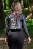 Woman back with a black leather jacket with handmade flower motive decoration in the forest on spring sunny day. Young girl back with a black leather jacket with royalty free stock photo