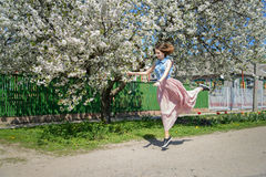 Young girl on the background of a blossoming cherry tree Royalty Free Stock Photography