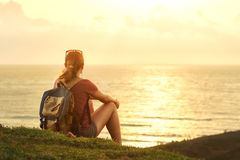 Young girl with backpack enjoying sunset listening to music on p Stock Image