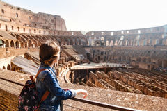 Young girl with backpack exploring inside the Coliseum. Young girl with backpack exploring inside the Colosseum Coliseum. Rome, Italy Royalty Free Stock Photography