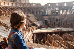 Young girl with backpack exploring inside the Colosseum Royalty Free Stock Photography